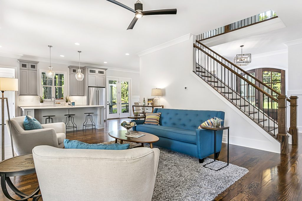 Photograph by Gray Scale Services of gorgeous living room to kitchen with light grey walls, modern furniture, and dark brown hardwood floors. Measuring Homes in Charlotte NC area.