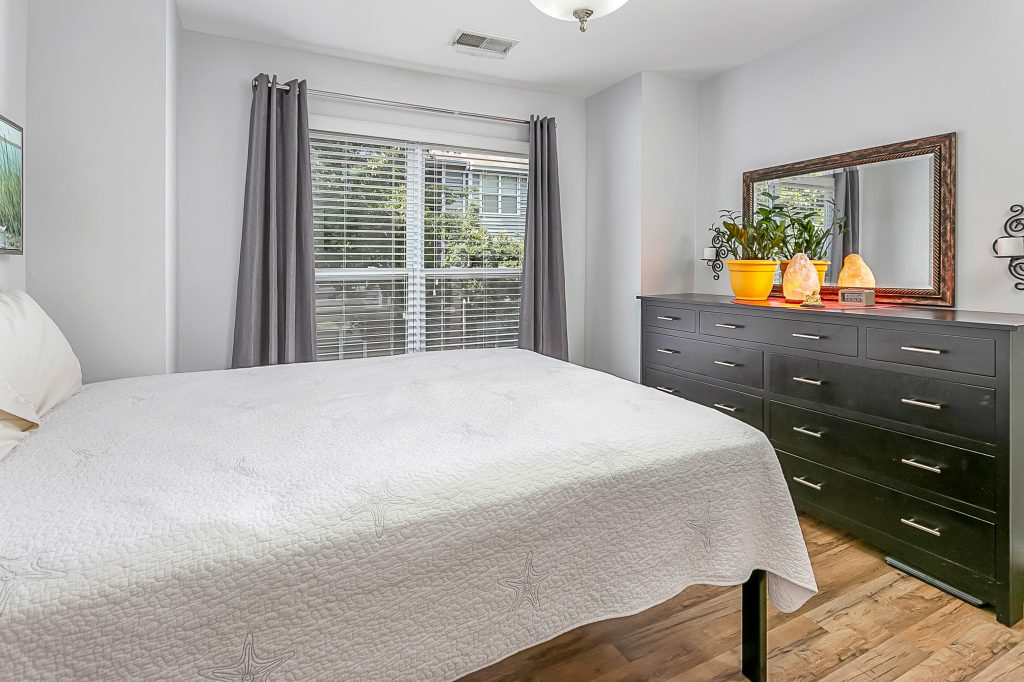 Bedroom view showing updated flooring, attractive gray paint, and trees outside the window.