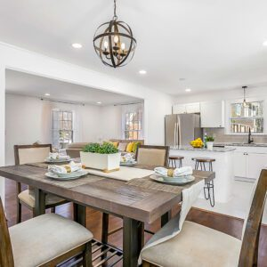Image is of white walls and ceiling, reddish brown hardwood floors hosting a rustic table and chairs with circular iron chandelier over the table. In the background of image is the kitchen and living room in the background. Interested in a Zillow 3D Tour of your home or listing? Order today!