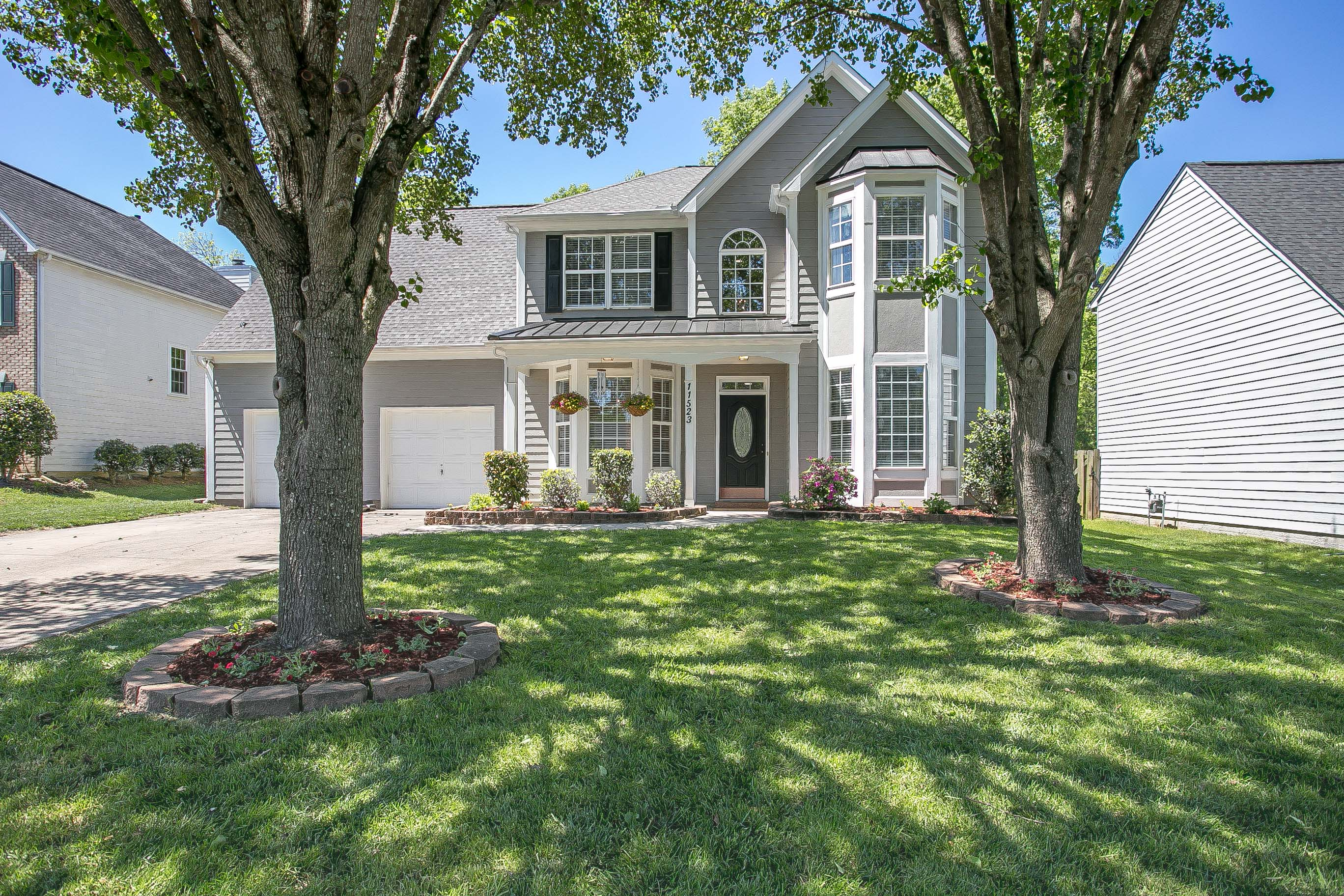 Real estate pictures of this gorgeous home shows a two story grey colored house with white trim, black shutters and black front door overlooking a front lawn with two shade trees.