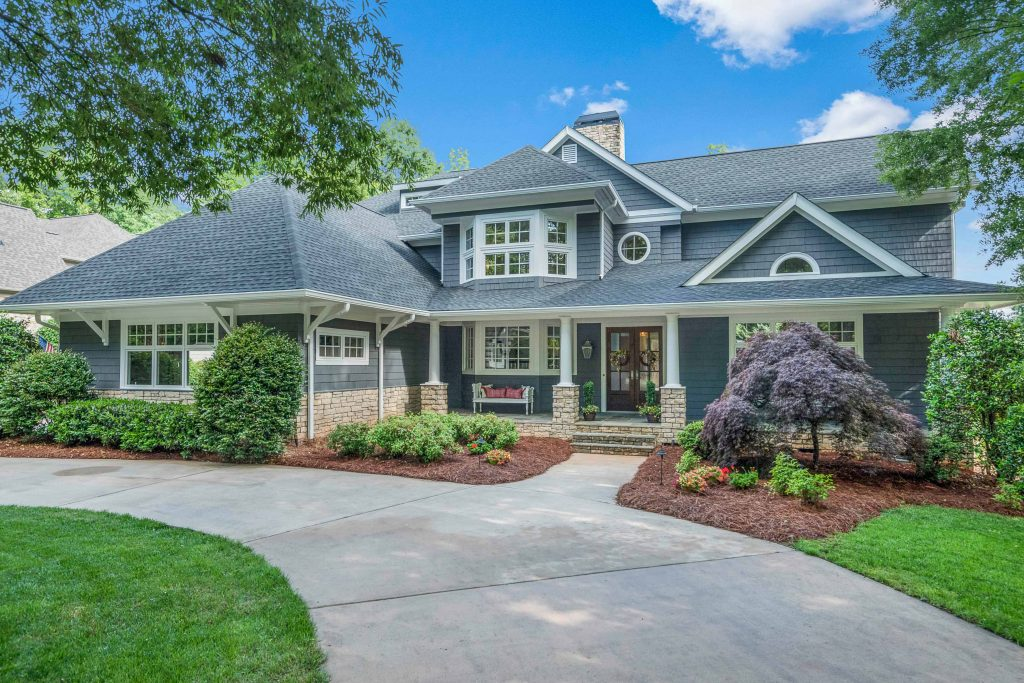 This photo is of a home with sweeping driveway approaching a grand gray/blue house, and was taken by a Zillow Certified Photographer at Gray Scale Services.