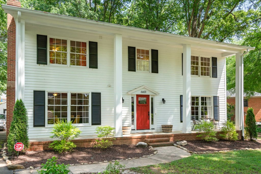 Gorgeous two story plantation style home painted white with a red front door, and has black shutters on the windows.