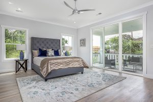 Professional real estate photographer is Gray Scale Services. Image is of a large master bedroom with grey walls, white ceiling, laminate hardwood floors, two windows on either side of the bed, and sliding glass door that leads to the second story porch.