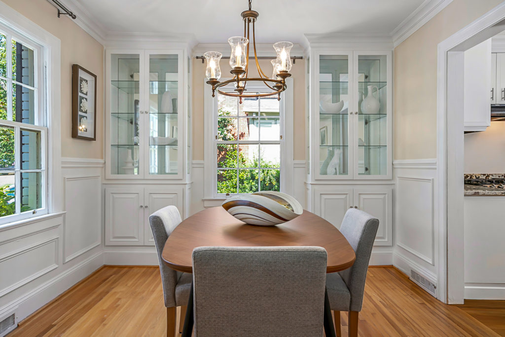 Professional real estate photographer is Gray Scale Services. Image is a straight on shot of a dining room with a view of two white built in cabinets on either side of the window on the far wall. The table is an oval-rectangular shape and has one grey-colored covered chair on each side of the table. The walls are a pale yellow on the upper half with white wainscoting on the lower half, and floors are hardwood..